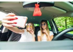 在驾驶汽车和采取selfie的汽车旅行的两个少_8471775
