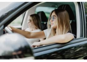 汽车旅行的两个少妇驾驶汽车和做乐趣积极_8471796
