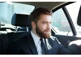 坐在汽车的年轻微笑的商人_7858062