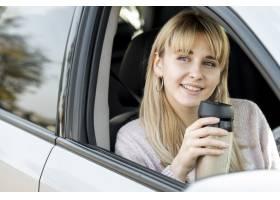 坐在汽车的美丽的白肤金发的妇女_5999617