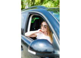 太阳镜的美丽的少妇驾驶她的汽车_8471792
