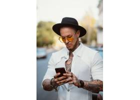 帽子和太阳镜的一个年轻人在手里拿着手机_8591704
