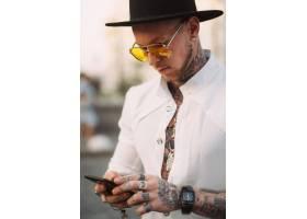 帽子和太阳镜的一个年轻人在手里拿着手机_8591731