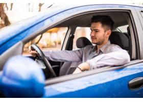 微笑的年轻人佩带的玻璃坐在他的汽车的轮子_8472257
