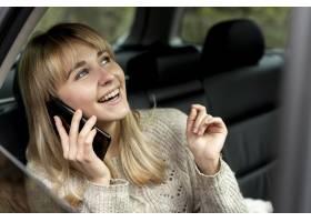 微笑的白肤金发的妇女谈话在电话_5999572