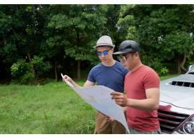 站立乘坐在农村路的亚裔男性朋友和看大地图_5839056