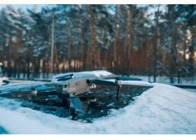 站立在一辆积雪的汽车的屋顶上的quadrocopt_7528839