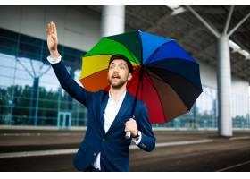 拿着杂色的伞捉住的汽车的年轻商人的图片在_7838515
