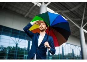 拿着杂色的伞的年轻商人的图片寻找汽车在驻_7838516