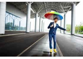 拿着杂色的伞的年轻商人的图片捉住汽车在机_7838508