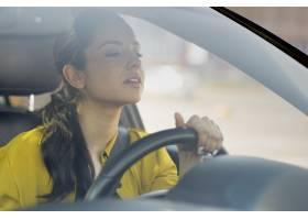 司机妇女看在她的汽车前面_7750792