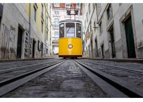 黄色电车走在旧建筑周围的一个狭窄的胡同_8281343