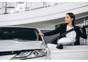 选择一辆汽车的妇女在汽车陈列室_5852274