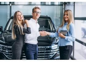 选择一辆汽车的年轻夫妇在汽车展览室_5915132