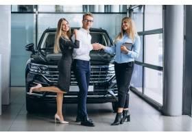 选择一辆汽车的年轻夫妇在汽车展览室_5915134