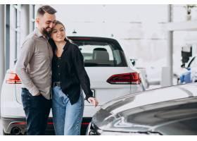 选择一辆汽车的年轻夫妇在汽车展览室_7167984