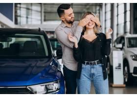 选择一辆汽车的年轻夫妇在汽车展览室_7167991