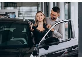 选择一辆汽车的年轻夫妇在汽车展览室_7168677