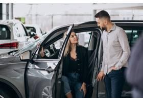 选择一辆汽车的年轻夫妇在汽车展览室_7168682