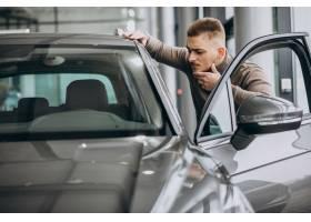 选择一辆汽车的年轻英俊的人在汽车陈列室_7200246