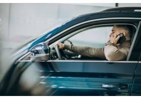 选择一辆汽车的年轻英俊的人在汽车陈列室_7200762