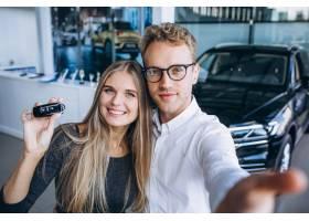 选择一辆汽车的男人和妇女在汽车陈列室_5915137