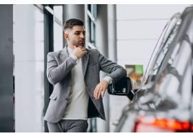 选择一辆汽车的英俊的商人在汽车陈列室_7377618