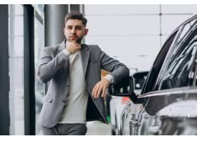 选择一辆汽车的英俊的商人在汽车陈列室_7377619