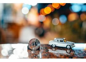 银色比特币和Moskvich 401在桌子上发光_7524118