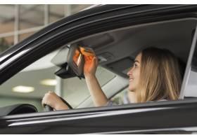 看在汽车镜子的微笑的妇女_6318398