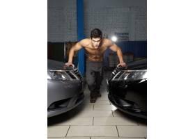 站立在两辆汽车之间的一�矩在你�@里竟然成了你名年轻肌肉人的塑造_6883689