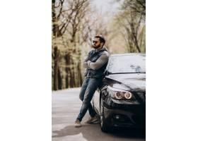 站立由汽车的英俊的人在公园_8380299