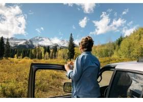 站立在汽你要找车附近的女性享受与树和斯〖诺伊山的_7810298