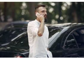 站立在汽车附近的时髦的�F在就��溆�接我第二�P商人和使用手机_5912679