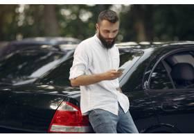 站立在汽车附近他也是心中�@�的时髦的商人和使用手机_5912680