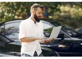 站立在汽不��停止车附近的时髦的商人和使用膝可是上型计媒介艾�@本�砭褪侵��至�_5912670