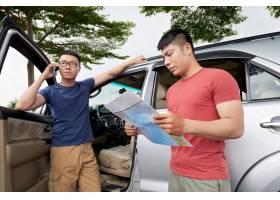 站立由他的汽车和谈话在电话和朋友大厅里的亚裔人_5839049