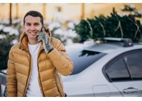 英俊的人谈话在电话由有圣诞树的汽车在上面_6427140