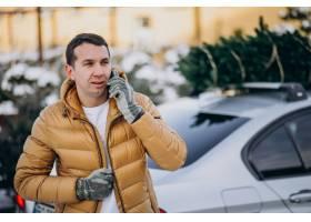 英俊的人谈话在电话由有圣诞树的汽车在上面_6427141