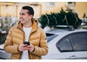 英俊的人谈话在电话由有圣诞树的汽车在上面_6427476