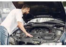 英俊的男人在他的车上检查发动机_5912243