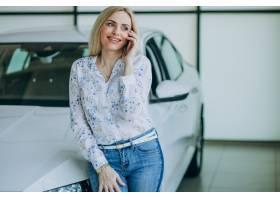 有电话的美丽的妇女在汽车陈列室_7869634