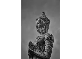灰色射击了一个菩萨雕象在黑暗的天空下_8280999