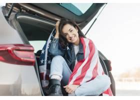 拿着在什么汽车树干的微笑的妇女大美国旗子_7968585