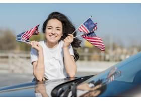 拿着在汽车的中间射击妇女美国旗子_7968396