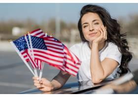 拿着在汽车的中间射击深色的妇女美国旗子_7968397