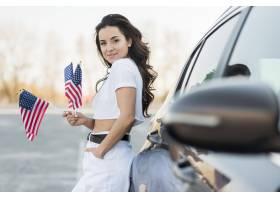 拿着美国旗子的中间射击深色的妇女在汽车附_7968394