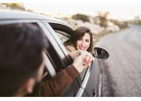 握手的男人和妇女在汽车外面_6209508
