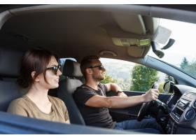 微笑的年轻夫妇坐在汽车享受山景_7780943
