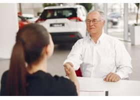 坐在汽车沙龙和谈话与经理的老人_7377055